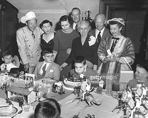 David Eisenhower blows out the candles on his birthday cake at a cowboy-themed party in the White House, Washington DC, March 31, 1956. Among the...