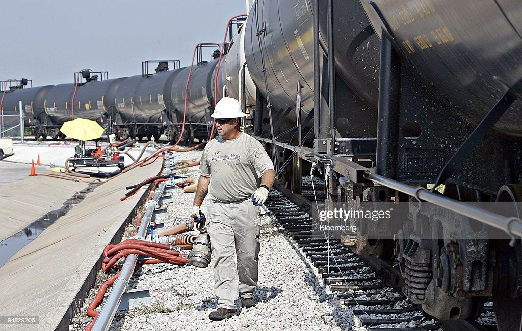 David Etzel carries a pipe fitting as he walks alongside rai : ニュース写真