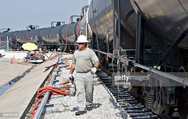 David Etzel carries a pipe fitting as he walks alongside railroad tankers containing ethanol at the Bayport Rail Terminal in Pasadena, Texas, U.S.,...