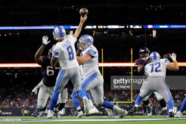 David Fales of the Detroit Lions throws a pass under pressure by Albert Huggins of the Houston Texans in the third quarter during the preseason game...