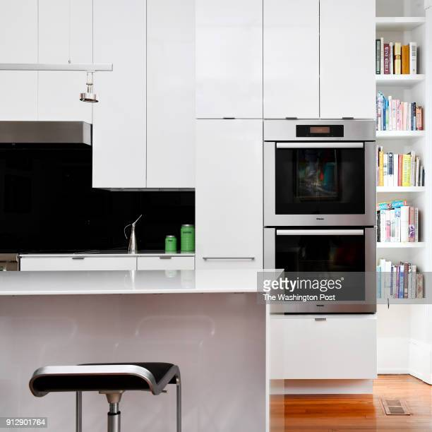 David Feinstein and Susan Pitman's renovated kitchen has a large island and a built in bookshelf seen January 04 2018 in Washington DC