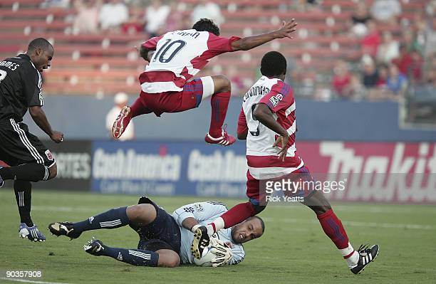 David Ferreira of the FC Dallas leaps over goalie Josh Wicks of the DC United as he blocks the ball while Jeff Cunningham of the FC Dallas looks on...