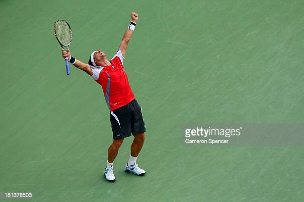 David Ferrer of Spain celebrates match point against Janko Tipsarevic of Serbia during their men's singles quarterfinal match Day Eleven of the 2012...