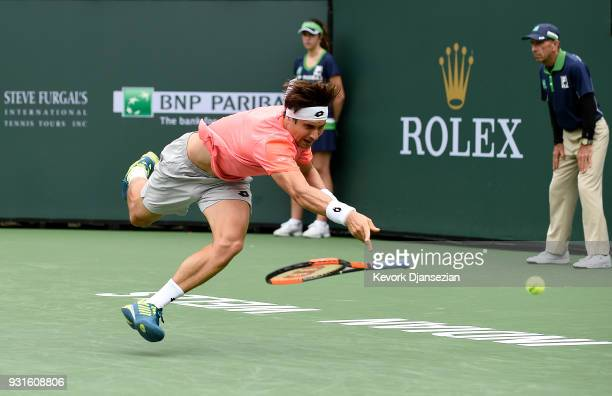David Ferrer of Spain dives and falls as he attempts to return against Juan Martin Del Porto of Argentina during Day 9 of BNP Paribas Open on March...