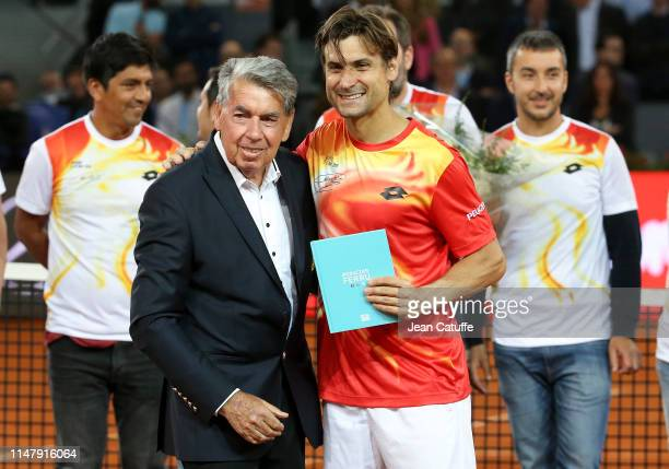 David Ferrer of Spain is congratulated by tennis legend Manolo Santana during a farewell ceremony following his last match on tour against Alexander...