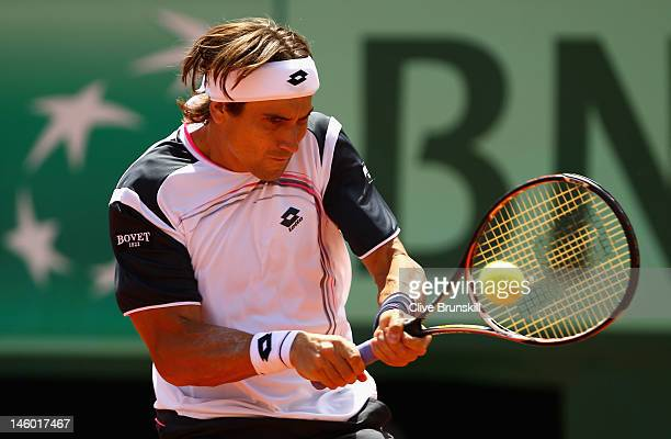David Ferrer of Spain plays a backhand in his men's singles semi final match against Rafael Nadal of Spain during day 13 of the French Open at Roland...