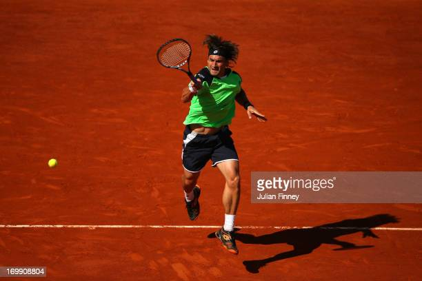 David Ferrer of Spain plays a forehand in his Men's Singles quarter final match against Tommy Robredo of Spain during day ten of the French Open at...