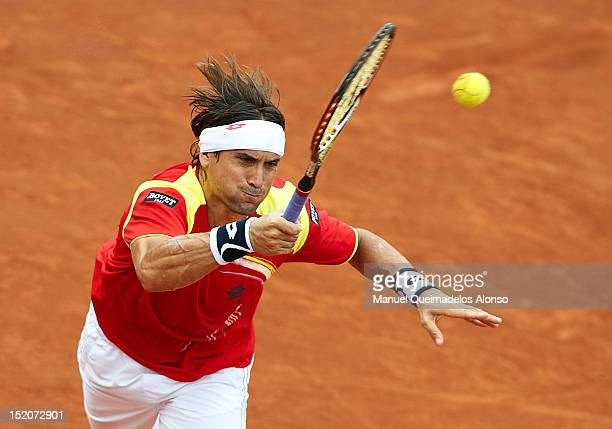 David Ferrer of Spain returns a shot to John Isner of the United States during day three of the semi final Davis Cup between Spain and the United...