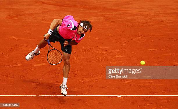 David Ferrer of Spain serves in his men's singles semi final match against Rafael Nadal of Spain during day 13 of the French Open at Roland Garros on...