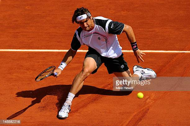 David Ferrer of Spain slides across the clay to play a fopehand during his men's singles third round match against Mikhail Youzhny of Russia during...