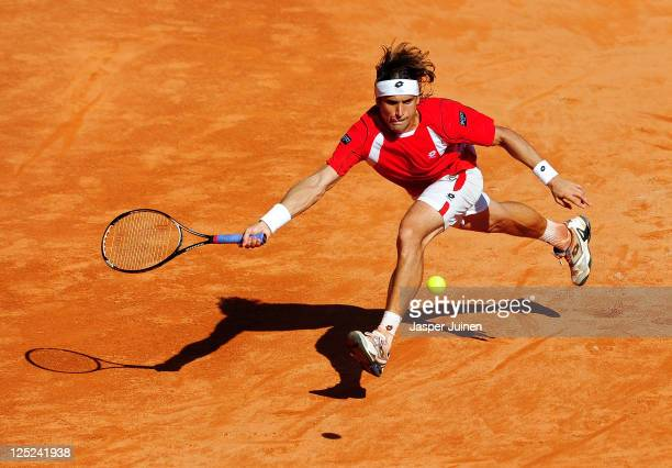 David Ferrer of Spain stretches to play a backhand to Gilles Simon of France during day one of the semi final Davis Cup match between Spain and...