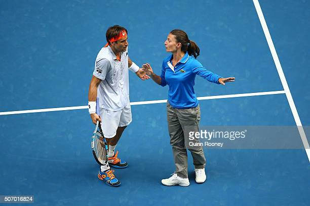 David Ferrer of Spain talks with the chair umpire before a break in play while the roof on Rod Laver Arena closes as storms hit Melbourne in his...