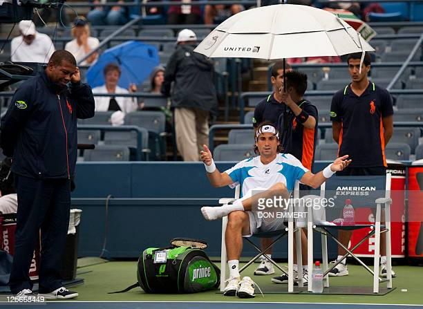 David Ferrer of Spain waits while it rains during his Men's singles match against Andy Roddick of the US at the 2011 US Open tennis tournament...