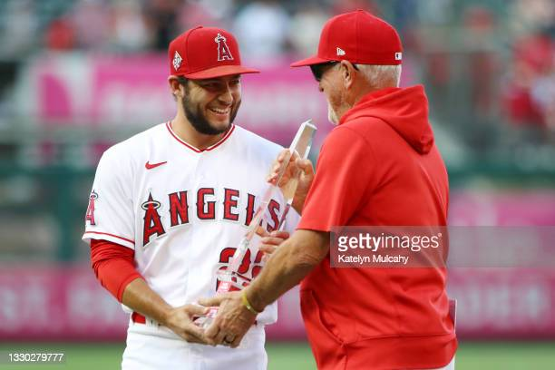 David Fletcher of the Los Angeles Angels holds the Player of the Week trophy with manager Joe Maddon of the Los Angeles Angels before the game...