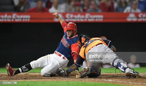 David Fletcher of the Los Angeles Angels of Anaheim crosses the plate before Martin Maldonado of the Houston Astros can make the tag in the eighth...