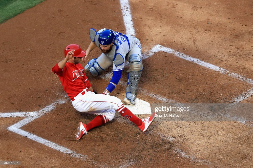 David Fletcher #6 of the Los Angeles Angels of Anaheim is tagged out at homeplate by Russell Martin #55 of the Toronto Blue Jays during the third inning of a game at Angel Stadium on June 23, 2018 in Anaheim, California.