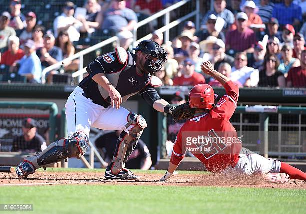 David Fletcher of the Los Angeles Angels of Anaheim is tagged out sliding into home plate by Adam Moore of the Cleveland Indians during the ninth...