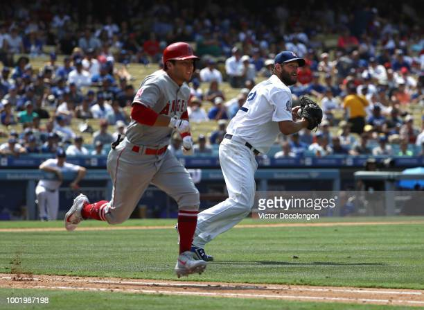 David Fletcher of the Los Angeles Angels of Anaheim runs to first base on his sacrifice bunt as pitcher Clayton Kershaw of the Los Angeles Dodgers...