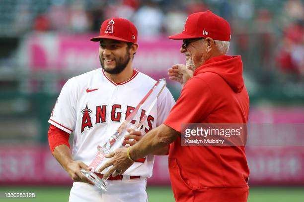 David Fletcher of the Los Angeles Angels poses with the Player of the Week trophy with manager Joe Maddon of the Los Angeles Angels before the game...