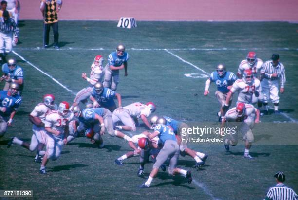 David Francis of the Ohio State Buckeyes blocks for teammate Paul Warfield during an NCAA game against the UCLA Bruins on October 6, 1962 at the Los...