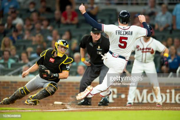 David Freeman of the Atlanta Braves slides into home plate past Francisco Cervelli of the Pittsburgh Pirates at SunTrust Park on September 1 2018 in...
