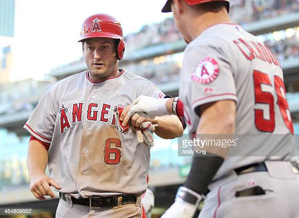 David Freese of the Los Angeles Angels is congratulated by Kole Calhoun of the Los Angeles Angels after Freese scored in the second inning during...