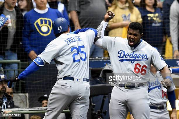 David Freese of the Los Angeles Dodgers celebrates with Yasiel Puig after hitting a solo home run against Wade Miley of the Milwaukee Brewers during...