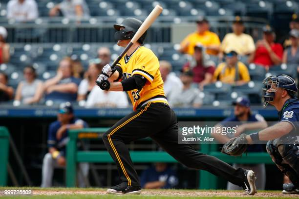 David Freese of the Pittsburgh Pirates hits a RBI triple in the ninth inning against the Milwaukee Brewers at PNC Park on July 15 2018 in Pittsburgh...