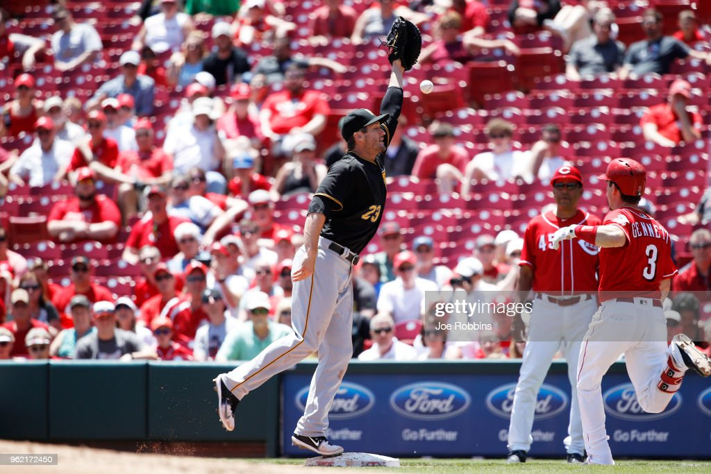David Freese #23 of the Pittsburgh Pirates misses the throw to first allowing Scooter Gennett #3 of the Cincinnati Reds to be safe in the third inning at Great American Ball Park on May 24, 2018 in Cincinnati, Ohio. The Reds won 5-4.