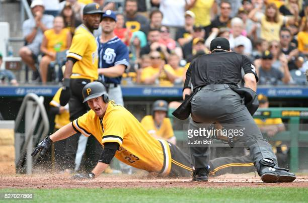 David Freese of the Pittsburgh Pirates slides into home plate on an RBI double by Jose Osuna in the third inning during the game against the San...
