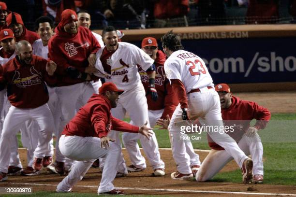David Freese of the St Louis Cardinals celebrates at home plate after hitting a walk off solo home run in the 11th inning to win Game Six of the MLB...