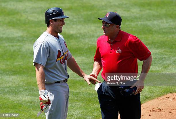 David Freese of the St Louis Cardinals has his left hand tended to by a trainer after taking a pitch off his knuckles in the sixth inning against the...