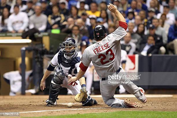 David Freese of the St Louis Cardinals scores against Jonathan Lucroy of the Milwaukee Brewers on a sarifice fly hit by Adron Chambers in the top of...