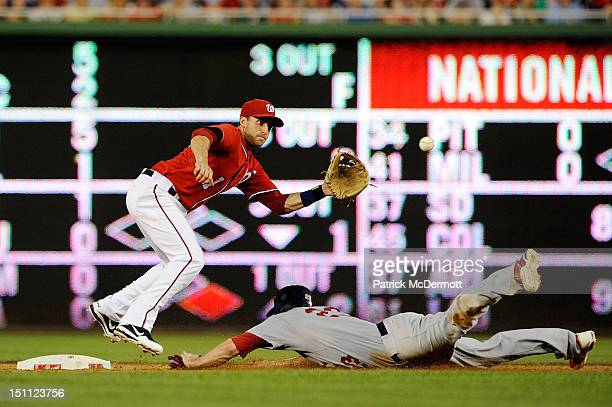 David Freese of the St Louis Cardinals steals second base against Stephen Lombardozzi of the Washington Nationals in the ninth inning during a game...