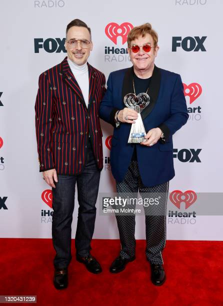 David Furnish and honoree Elton John attend the 2021 iHeartRadio Music Awards at The Dolby Theatre in Los Angeles, California, which was broadcast...