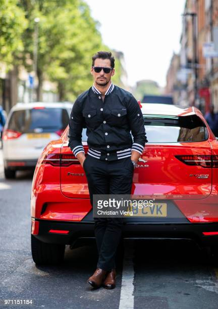 David Gandy wearing college jacket in front of a Jaguar is seen during London Fashion Week Men's June 2018 on June 10 2018 in London England