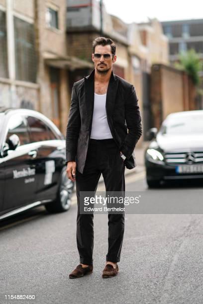 David Gandy wears a blazer jacket, a white t-shirt, sunglasses, during London Fashion Week Men's June 2019 on June 09, 2019 in London, England.