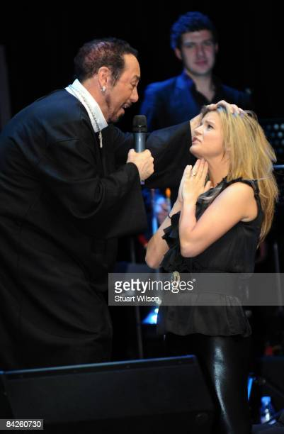 David Gest performs a mock Baptism on Kerry Katona during a performance of 'David Gest My Life' at the O2 Arena on January 12 2009 in London England