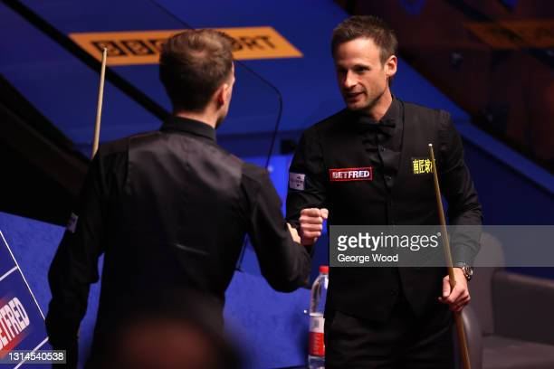 David Gilbert of England interacts with Judd Trump of England following the Betfred World Snooker Championship Round Two match between David Gilbert...