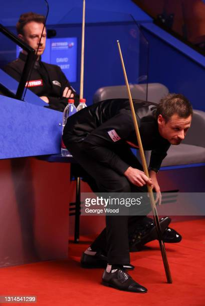 David Gilbert of England prepares to play a shot as Judd Trump of England watches on behind during the Betfred World Snooker Championship Round Two...