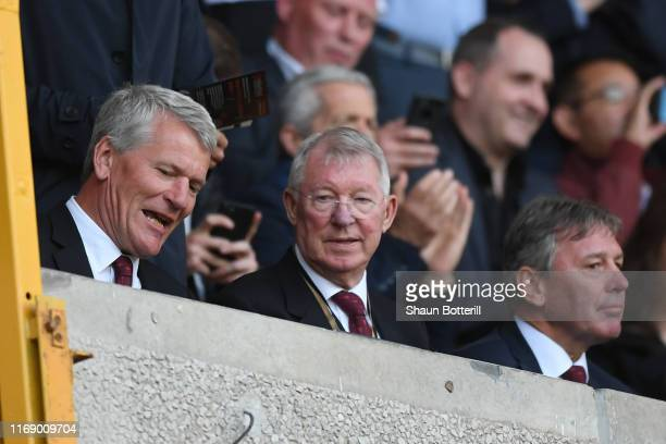 David Gill, Sir Alex Ferguson and Bryan Robson look on from the stands during the Premier League match between Wolverhampton Wanderers and Manchester...