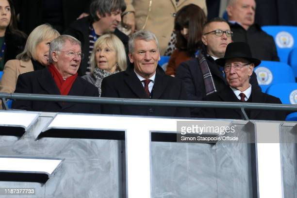 David Gill sits in between Former Man Utd manager Sir Alex Ferguson and Sir Bobby Charlton during the Premier League match between Manchester City...