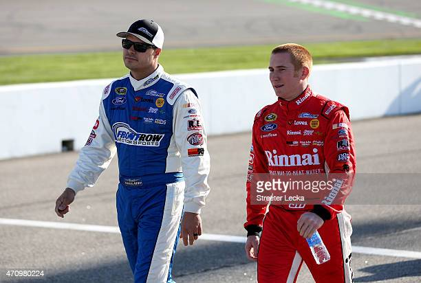 David Gilliland, driver of the The Pete Store Ford, and Cole Whitt, driver of the Front Row Motorsports Ford, walk on the grid during qualifying for...