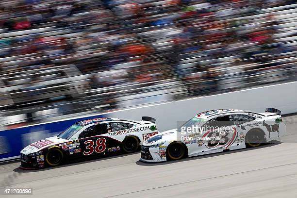 David Gilliland, driver of the The Pete Store Ford, leads Matt DiBenedetto, driver of the Dan Bilzerian Toyota, during the NASCAR Sprint Cup Series...