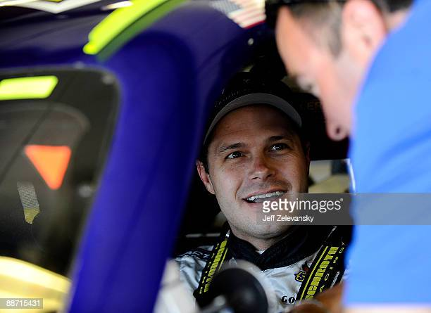 David Gilliland driver of the TRG Motorsports Chevrolet talks to a crew member in the garage during practice for the NASCAR Sprint Cup Series LENOX...
