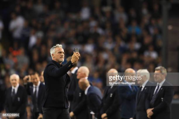 David Ginola films with with his phone as he walks onto the pitch during the closing ceremony after the Premier League match between Tottenham...