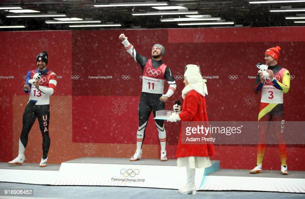 David Gleirscher of Austria celebrates at the flower ceremony after winning the gold following run 4 during the Luge Men's Singles on day two of the...