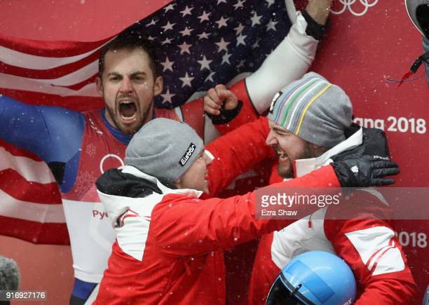 David Gleirscher of Austria is congratulated by a teammates after winning gold while Chris Mazdzer of the United States celebrates in the background...