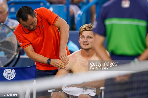 David Goffin has his shoulder worked on during a break in play in his semifinal match against Roger Federer at the Western Southern Open at the...