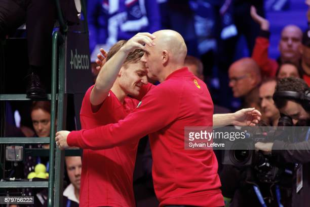 David Goffin of Belgium celebrates with team coach Johan Van Herck winning his match against JoWilfried Tsonga of France during day 3 of the Davis...